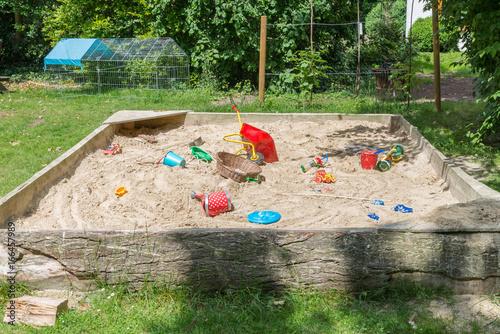 Fotografie, Obraz  Großer Sandkasten mit Kinderspielzeug in einem Garten