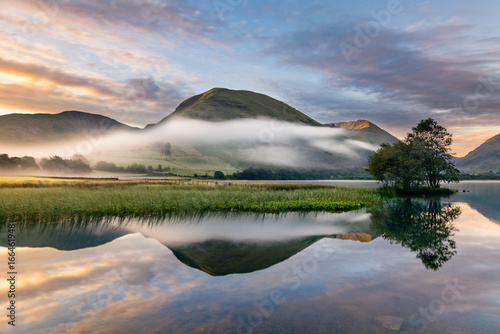 Foto auf Gartenposter See / Weiher A beautiful summer sunrise with early morning mists rolling through valley in the English Lake District.