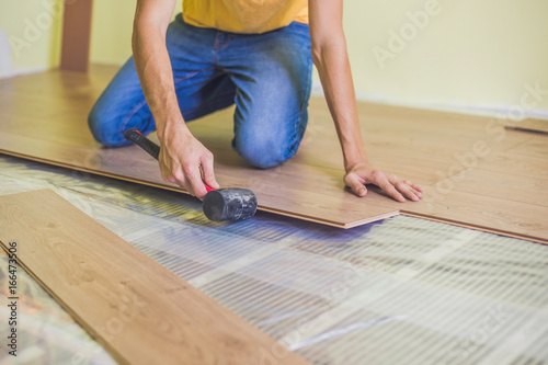 Man Installing New Wooden Laminate Flooring Infrared Floor Heating