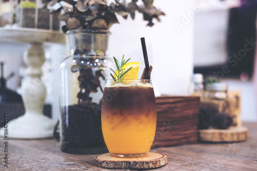 Fotomural Closeup image of a glass of orange cold brew coffee on wooden table