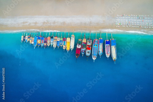 Deurstickers Luchtfoto Aerial view of colorful boats in mediterranean sea in Oludeniz, Turkey. Beautiful summer seascape with ships, clear azure water and sandy beach in sunny day. Top view of yachts from flying drone