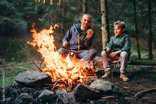 Father and son roast marshmallow on campfire Fotobehang