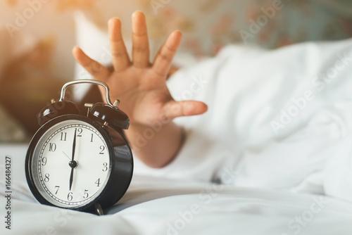 Plakat Ręka kobiety pod kocem wyciąga budzik.