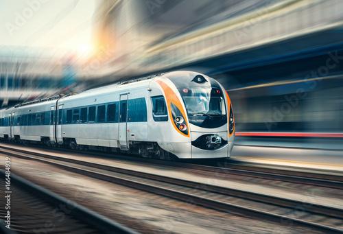 Fototapeta High speed train in motion at the railway station at sunset obraz na płótnie