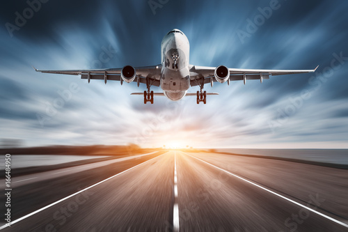 Poster Avion à Moteur Airplane and road with motion blur effect at sunset. Landscape with passenger airplane is flying over the asphalt road and cloudy sky. Commercial plane is landing. Aircraft with blurred background