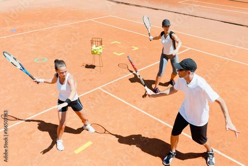 Tennis instructor explaining forehand