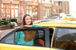 Young smiling girl standing near taxi car
