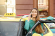 Young woman standing near taxi car and talking on phone
