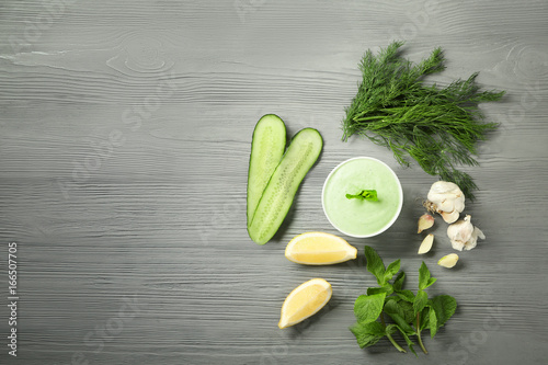 Delicious yogurt sauce in bowl with ingredients on wooden background