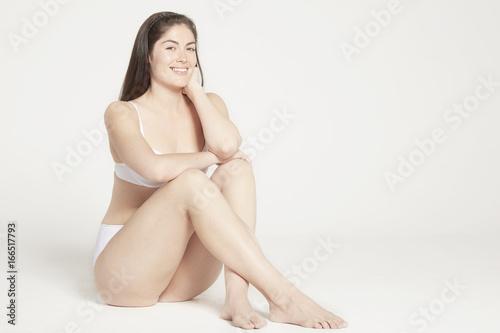 Model sitting in white underwear.