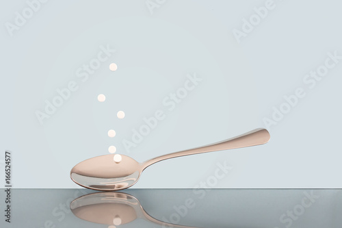 Photo Aspartame sweetener, tablet, on spoon. Pale blue background.