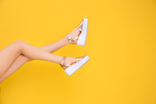 Female Legs In Stylish Shoes On Color Background