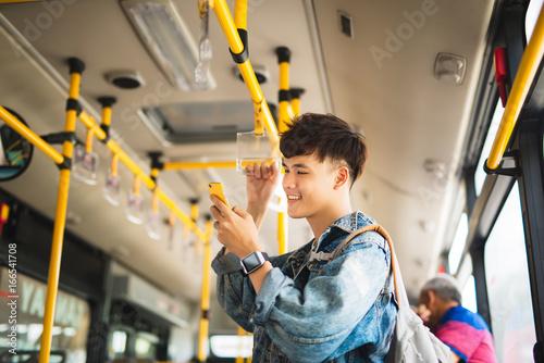 Zdjęcie XXL Azjatycki człowiek biorąc transport publiczny, stojąc wewnątrz autobusu.