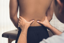 Therapist Giving Massage To Back Pain Patient In Clinic