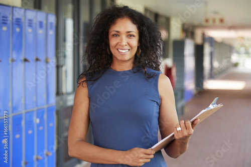 Fototapeta Middle aged black female teacher smiling in school corridor