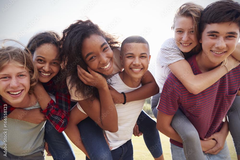 Fototapeta Teenage school friends having fun piggybacking outdoors