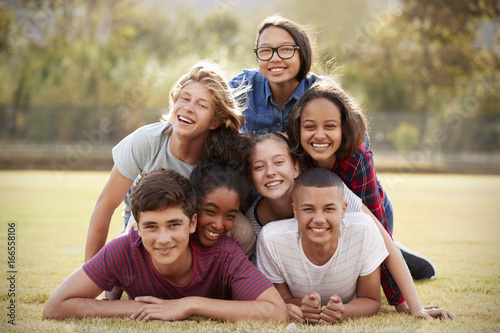 Fotografía  Group of teenage friends lying in a pile on grass