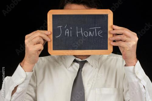 Fotografía  Homme cachant son visage avec une ardoise sur laquelle est écrit j'ai honte