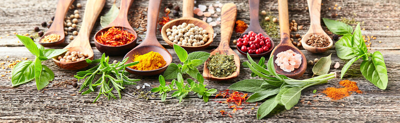 Spices and herbs on a woode...