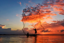 Silhouetted Fisherman Fishing ...