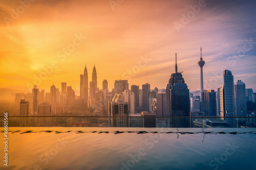 Cityscape of Kuala lumpur city skyline with swimming pool on the roof top of hotel at sunrise in Malaysia Poster