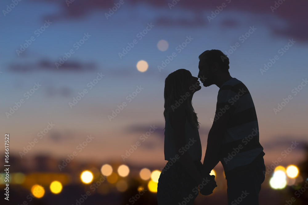 Fototapety, obrazy: Silhouettes of a young couple kissing with city panorama in the background.