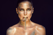 Close Up Portrait Of Beautiful Woman With Yellow Eyes, Artistic Snake Skin Make Up And Sleek Hair Holding Luxurious Golden Necklace In Her Mouth. Jewellery Concept. Studio Shot