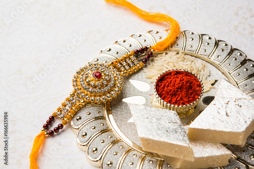 Photo  Raksha Bandhan greeting - Rakhi and gift with sweet kaju katli or mithai and rice grains & kumkum in a decorative plate
