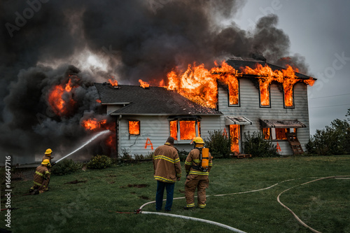 Tablou Canvas Fire Fighters Putting Out A House Fire