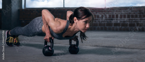 Fotografía  Young woman athlete in sportswear push ups with dumbbells
