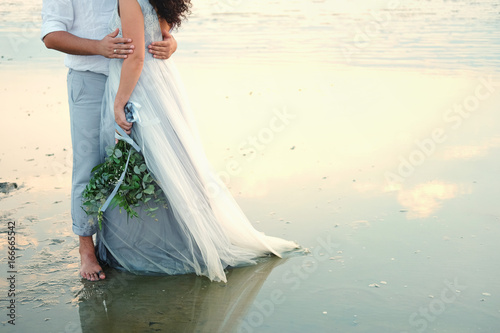 Fotografie, Obraz Couple of lovers embracing standing barefoot in shallow water