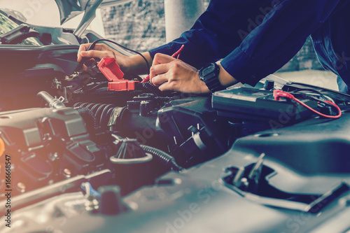 Photo Auto mechanic checking car battery voltage