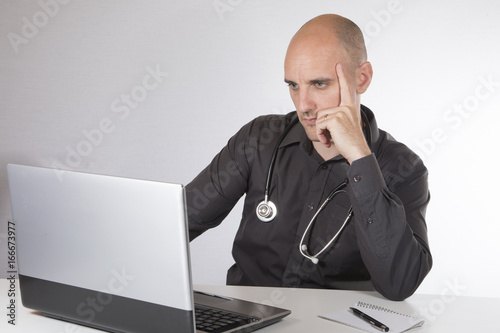 Fotografia, Obraz  Doctor sitting working at his laptop computer