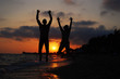 Couple jumping on beach at sunset. Happy people on the sea. Summer vacation concept