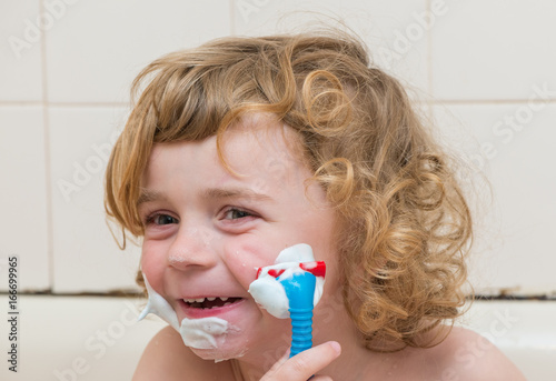 Happy little boy pretending to shave with a toy razor at bath time ...