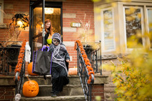 Boy Going Door To Door Trick Or Treat At Halloween