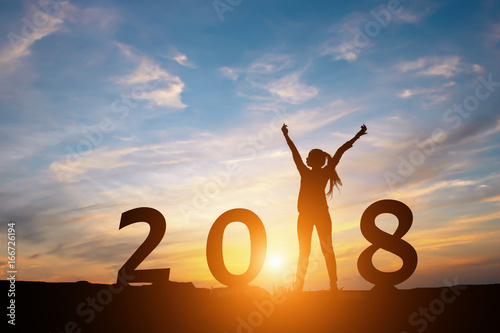 Fotografia, Obraz  Silhouette of happy woman with New yeay 2018 concept in sunset background