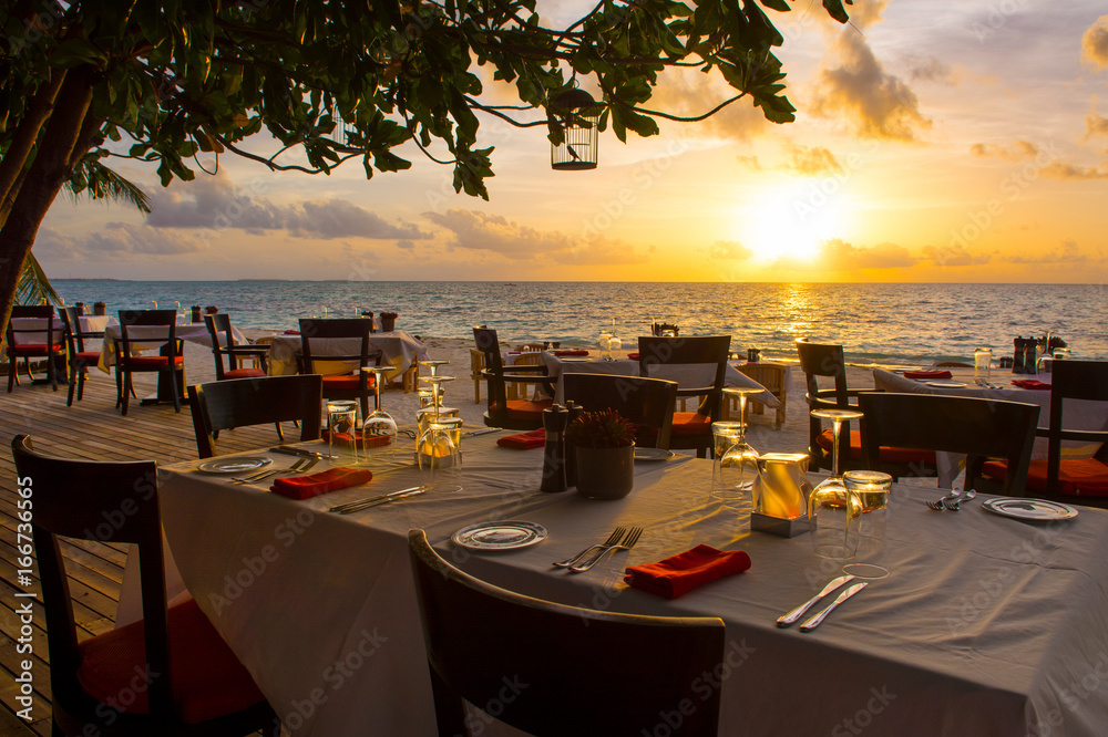 Fototapety, obrazy: Tropical restaurant on the sandy beach. Landscape of beautiful sunset in Maldives island with colorful sky and dramatic clouds over wavy sea.