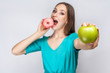 Beautiful young woman with freckles in green dress, eating pink donut and holding green apple. studio shot on light gray background