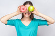 Beautiful young woman with freckles in green dress, holding before her eyes green apple and pink donut and shows her teeth. studio shot on light gray background.