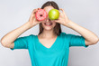 Beautiful young woman with freckles in green dress, holding before her eyes green apple and pink donut with toothy smile. studio shot on light gray background.