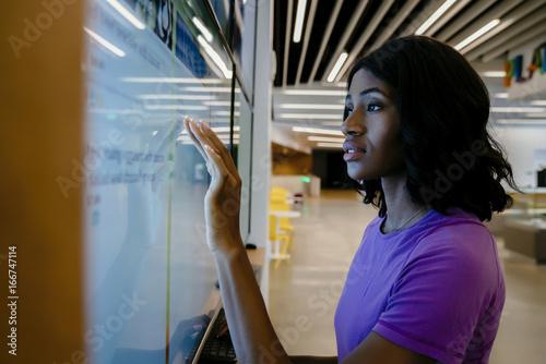 Fotografering  Woman touching large computer screen monitor