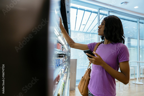 Woman in convenience store on cell phone Canvas Print