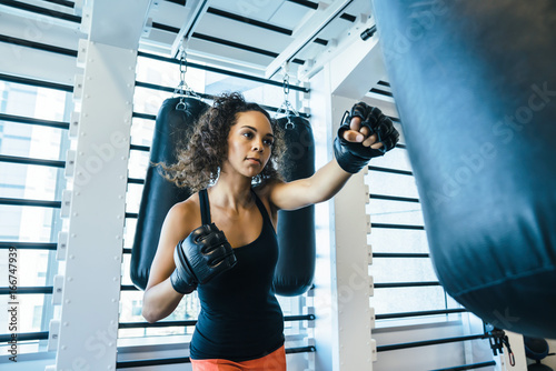 Fotografie, Obraz  Woman hitting boxing bag in gym