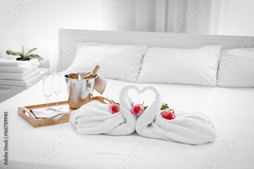 Poster Cygne Composition of two towel swans, flowers and ice bucket with champagne on bed in hotel room