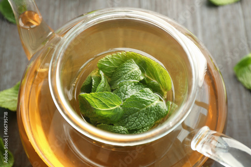 Poster Thee Teapot of hot aromatic tea with lemon balm on wooden table