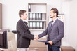 Young Business partners shaking hands in the office. Two businessman in formal suits shaking hands in corporate office eviroment
