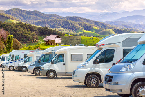Close up motorhomes parked in a row on background green terraced rice field nature landscape Fototapete
