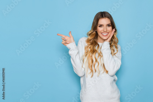 Smiling Young Woman In Pastel Sweater Is Pointing