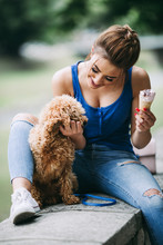 Beautiful Smiling Young Woman Eating Ice Cream And Enjoying With Her Little Red Poodle Puppy.